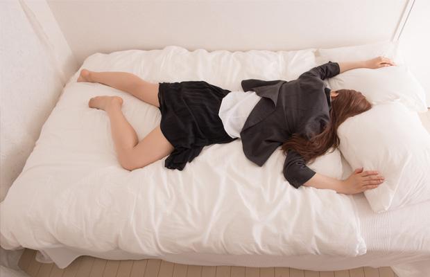 ベッドに倒れ込む看護師
